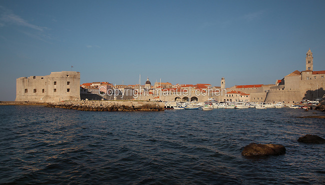 The old harbour of the medieval walled city, protected by the 14th century Fortress of St John or Mulo Tower and the Porporela breakwater (left), Dubrovnik, Croatia. The city developed as an important port in the 15th and 16th centuries and has had a multicultural history, allied to the Romans, Ostrogoths, Byzantines, Ancona, Hungary and the Ottomans. In 1979 the city was listed as a UNESCO World Heritage Site. Picture by Manuel Cohen