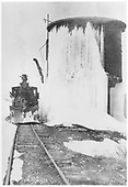 Front view of C&amp;S 2-6-0 #4 equipped with a wedge pilot plow at a winter-decorated water tank.<br /> C&amp;S