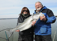 NWA Democrat-Gazette/FLIP PUTTHOFF <br /> Denise and Kevin Rivers, husband and wife striper-fishing guides at Beaver Lake, show a striper Denise caught Jan. 16, 2016 in the Rocky Branch area of Beaver Lake. The couple trolled slowly with large minnows to catch stripers during their trip.