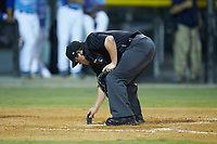 Umpire Chandler Durham cleans home plate during the game between the Johnson City Cardinals and the Burlington Royals at Burlington Athletic Stadium on September 3, 2019 in Burlington, North Carolina. The Cardinals defeated the Royals 7-2 to even Appalachian League Championship series at one game a piece. (Brian Westerholt/Four Seam Images)