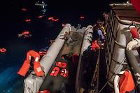 Die Sea Watch-2 Crew war am Freitag den 21. Oktober 2016 in den fruehen Morgenstunden waehrend ihrer 13. SAR-Mission vor der libyschen Kueste zu einer Position ausserhalb der 12 Meilenzone gerufen worden. Es war ein Fluechtlingsschlauchboot gesichtet worden. Als die Sea Watch-2 dort eintraf sah sie ca. 150 Menschen zusammengepfercht in einem ueberfuellten Schlauchboot sitzen. Eine Versorgung der Menschen auf dem Fluechtlingsschlauchboot mit Rettungswesten durch die Rettungs Boote der Sea Watch-2 wurde von der libyschen Kuestenwache unterbunden. Ein Soldat der Kuestenwache enterte das Schlauchboot vom Bug und machte sich dann an dem Aussenbordmotor zu schaffen. Auf dem Weg dahin schlug und trat er die Gefluechteten ein. Nach einigen Minuten entfernte sich das Boot der Kuestenwache. Dann verlor der Bug des Schlauchbootes seine Luft und es brach Panik bei den Gefluechteten aus. Sie sprangen in das Wasser und versuchten zum Schiff Sea Watch-2 zu gelangen. Die Crew warf ihnen Schwimmwesten und Rettungsringe zu, die Besatzungen der Rettungsboote der Sea Watch-2 zogen Menschen aus dem Meer, dennoch sind bis zu 30 Menschen ertrunken. Vier Ertrunkene konnten von der Sea Watch geborgen werden.<br /> Im Bild: Die Sea Watch-2 ist zum Fluechtlingsschlauchboot manoevriert worden. Im Fluechtlingsschlauchboot treibt mindestens ein lebloser Koerper mit dem Kopf unter Wasser. Einige Menschen konnten sich bereits an Bord retten. Im Wasser schwimmen Ertrunkene und Schwimmwesten. Oben am Bildrand sucht ein Rettungsboot der Sea Watch nach Menschen im Wasser.<br /> 21.10.2016, Mediterranean Sea<br /> Copyright: Christian-Ditsch.de<br /> [Inhaltsveraendernde Manipulation des Fotos nur nach ausdruecklicher Genehmigung des Fotografen. Vereinbarungen ueber Abtretung von Persoenlichkeitsrechten/Model Release der abgebildeten Person/Personen liegen nicht vor. NO MODEL RELEASE! Nur fuer Redaktionelle Zwecke. Don't publish without copyright Christian-Ditsch.de, Veroeffentlichung nur mit Fotografe