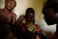 """Rosetta, 22 years old ( on left ) waits for her dose of brown brown, a mixture between cocaine and gunpowder while her friend Joanette, 22 years old inhales it  in an abandoned compound   in Monrovia, Liberia on  Wednesday March 21 2007..Melvin, 29 AKA """"Dad"""",  John, 29 AKA """"Desperate Soldier, Thomas 28 AKA """"Bullet Patrol"""", Leroy, 28, AKA """" Pussy Mechanic"""" and Steven 27 AKA """"Field Marshall"""" are all former child soldiers that found each other on the streets after the last round was fired in Liberia. Since then they """"Hustle"""" to put some food in their stomachs and buy some drugs to """" make them forget about their lives""""..ALL NAMES HAVE BEEN FICTIONALIZED TO PROTECT THE IDENTITIES OF THE 5 MEN."""