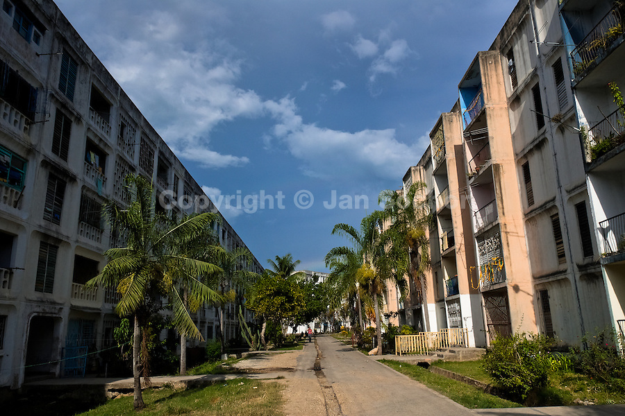 """Large apartment blocks are seen on both sides of the street in Abel Santamaría, a public housing suburb of Santiago de Cuba, Cuba, 31 July 2008. The Cuban economic transformation (after the revolution in 1959) has changed the housing status in Cuba from a consumer commodity into a social right. In 1970s, to overcome the serious housing shortage, the Cuban state took over the Soviet Union concept of social housing. Using prefabricated panel factories, donated to Cuba by Soviets, huge public housing complexes have risen in the outskirts of Cuban towns. Although these mass housing settlements provided habitation to many families, they often lack infrastructure, culture, shops, services and well-maintained public spaces. Many local residents have no feeling of belonging and inspite of living on a tropical island, they claim to be """"living in Siberia""""."""