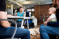 Mike Gutner (right), who handles operations at Mimo, his 10-month-old daughter Sadie Gutner as he speaks with Thomas Lipoma (center), Mimo co-founder and co-CTO, the Mimo headquarters Boston, Massachusetts, USA, on Mon., April 28, 2014. Sadie, daughter of Mike Gutner, is wearing one of the company's onesies, made by Mimo, which has a variety of sensors on it. The onesie has a detachable frog-shaped communication device that transmits data from the onesie's sensors and sends the data to a smartphone app, which displays information about the baby's respiration, skin temperature, position, and activity level. The onesie is washable and the device is water-resistant.