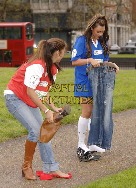 LEILANI DOWDING & MICHELLE HEATON.Photocall to promote the Soccer Six Event, which kicks off at West Ham on May 22nd and incudes celebrity football teams, aiming to encourage fans to be both fit and eat healthily..Hyde Park, London, April 19th 2004.full length kit shirt shorts socks football blue  funny changing jeans clothes brown knee high boots.Ref: PL.www.capitalpictures.com.sales@capitalpictures.com.©Capital Pictures