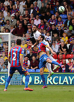 Pictured: Kyle Bartley of Swansea heads the ball over Scott Dann of Crystal Palace<br />