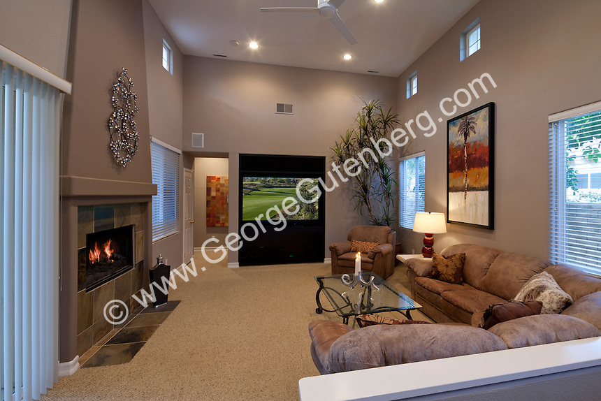Family room in modern home features a fireplace and big screen TV