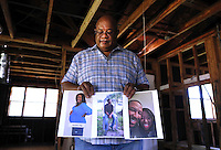 In this posed photograph Charles Brown holds pictures of his children, who have not moved back to New Orleans since Hurricane Katrina, inside his home in the Gentilly neighborhood of New Orleans, Louisiana, August 1, 2015. Almost ten years after Hurricane Katrina, Brown, who's house saw over 7 feet of flood water, has not been able to move back.   Brown currently lives in the Carrollton neighborhood of New Orleans with his wife while his children live in Houston, Texas.