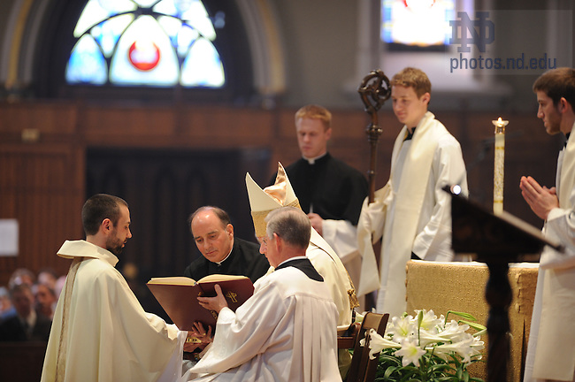 Rev. Andrew Gawrych, C.S.C. kneels before the Bishop at his ordination mass.