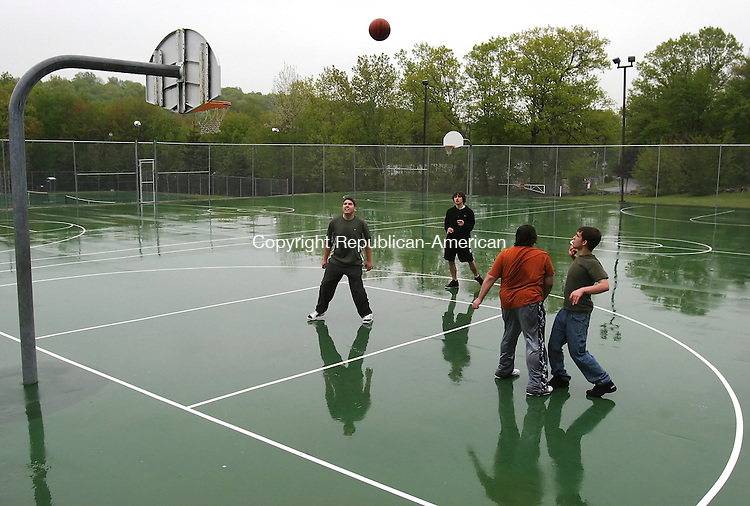 WOLCOTT, CT 05/20/08- 052008BZ04-  From left- Mac Tuttle, 20, Jason Williams, 20, Ian Williams, 17, and Albert Tamulonis, 17, watch a shot while playing basketball in the rain at Peterson Memorial Park in Wolcott Tuesday.   <br /> Jamison C. Bazinet Republican-American