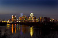 Austin, Texas downtown night city skyline with lights reflecting on the calm waters of Townlake from Travis Heights hills in Austin, Texas.