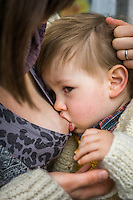 Close-up of a mother breastfeeding her 15 month old boy who is in a sling.<br /> <br /> London, England, UK<br /> 22-03-2015<br /> <br /> &copy; Paul Carter / wdiip.co.uk