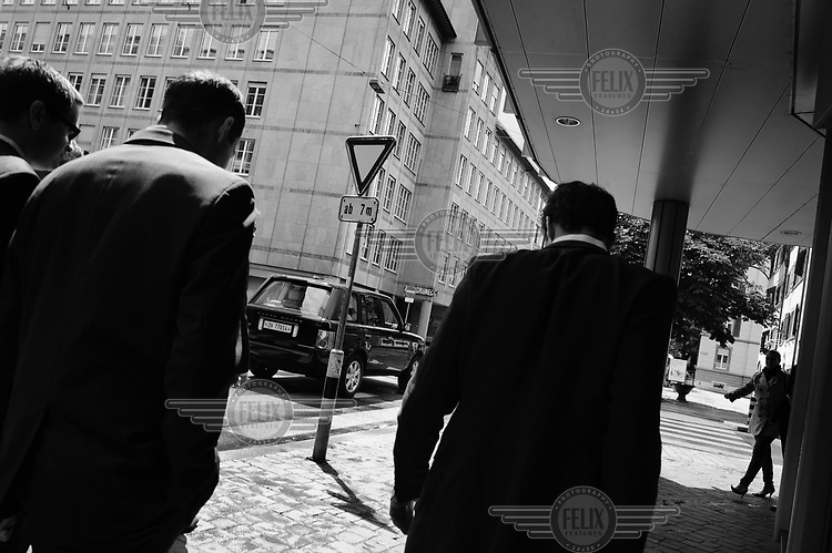 A group of bankers walk through Zurich's financial district.