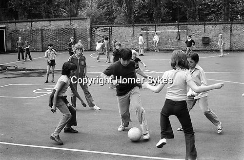School boys playing football in junior school playground lunch break South London England 1970s...