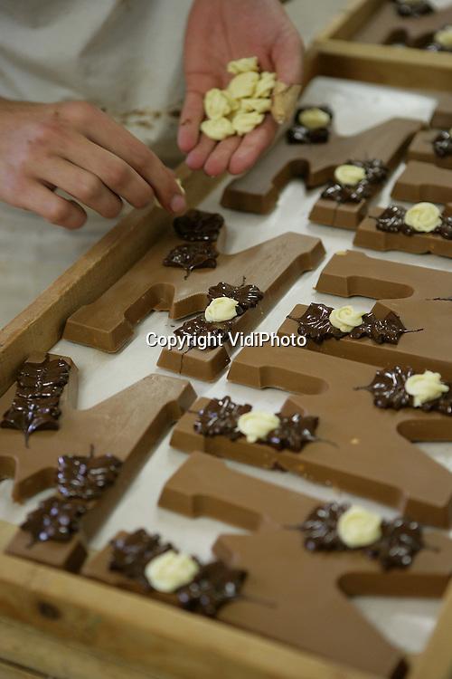Foto: VidiPhoto..GENDT - Personeel van chocoladefabriek Palino uit het Betuwse Gendt is volop bezig om de bestellingen voor Sinterklaas en Kerst af te werken. Chocola is populairder dan ooit en dat merkt ook de producent van luxe chocoladewerken. Door met name sterk gestegen consumptie in China en Oost-Europa worden de grondstoffen op de wereldmarkt fors duurder. De prijs van chocola zal volgend jaar in Nederland dan ook flink toenemen, verwacht Palino.