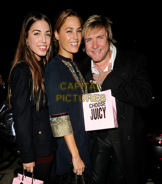 AMBER LE BON, YASMIN LE BON  & SIMON LE BON .At the Juicy Couture flagship store launch party, Bruton Street, London, England, UK, 13th October 2009..half length father daughter dad family lebon black pea coat red maroon dress  married mother mum mom husband wife burgundy shopping bags navy blue gold trim sleeves.CAP/CAN.©Can Nguyen/Capital Pictures.