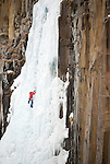 A young man ice climbing in Hyalite Canyon near Bozeman, Montana.