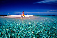 A couple (MR) with snorkel equipment enjoy a small private patch of paradise in Fiji.