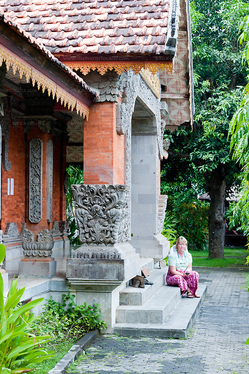 A tired tourist waits for her party (the photographer) on the front steps of the Buddhist temple at the top of the Bramavihara-Arama complex.