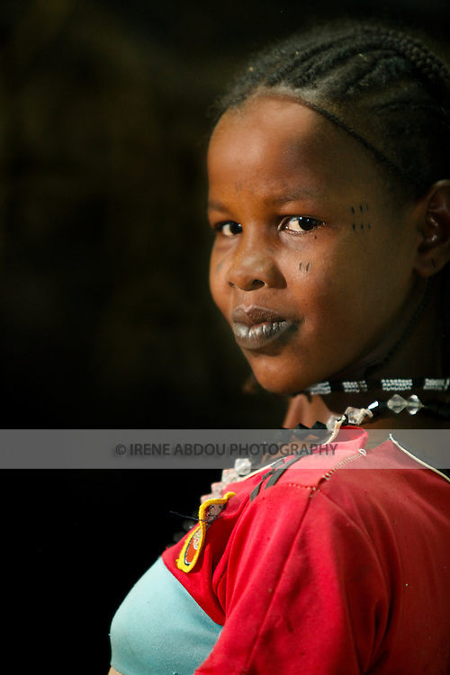 In the town of Djibo in northern Burkina Faso, a young Fulani woman peers into a house at night.