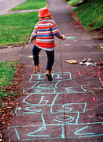 Young child playing hopscotch on sidewalk..MR