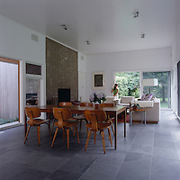 The dining table situated in the centre of the grey slate floor of the living area  is surrounded by mid-century bentwood chairs