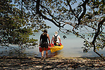 A couple carries their kayaks into the water off Indian Key, a park in the Florida Keys