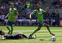 Seattle Sounders FC defender James Riley escapes the slide tackle of New England Revolution defender AJ Soares during during play at .CenturyLink Field in Seattle Sunday June 26, 2011. The Sounders won the game 2-1.   during play between the Seattle Sounders FC and the New England Revolution at .CenturyLink Field in Seattle Sunday June 26, 2011. The Sounders won the game 2-1.