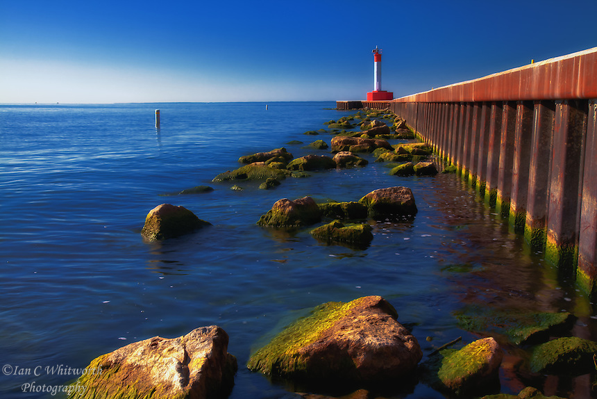 Low water in Lake Ontario reveals the rocks along side the Oakville lighthouse pier.