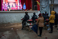 Local villagers watch a performance of the local Gan Opera in Poyang county at Poyang Lake, Jiangxi Province, December 2014. Poyang Lake, located in the north of Jiangxi Province, is the largest freshwater lake in China. It fluctuates dramatically between wet and dry seasons, from 3,500 square kilometres down to about 200 square kilometres. The lake provides a habitat for half a million migratory birds.