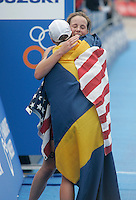 31 AUG 2007 - HAMBURG, GER - Lisa Norden (SWE) is congratulated on her victory by Jasmine Oeinck (USA - facing camera) - Under 23 Womens World Triathlon Championships. (PHOTO (C) NIGEL FARROW)