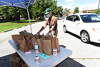 LEGION FOSTERS LEARNING<br />Charlie Breitzke (cq), a volunteer, delivers free lunches to patrons on Saturday Aug. 1 2020 during the second annual Bentonville-Centerton American Legion Post 77 school-supplies distribution event. Post members and volunteers distributed 117 bags of school supplies at the Center for Nonprofits in Rogers to families who preregistered to receive them. Lunch was provided to recipients and volunteers. Go to nwaonline.com/200802Daily/ to see more photos.<br />(NWA Democrat-Gazette/Flip Putthoff)