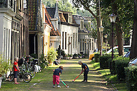 A young girl looks for  two boys play hoky at street in Amsterdam Noord on 9 September,2011.