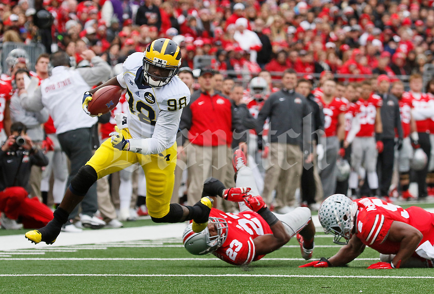 Michigan Wolverines quarterback Devin Gardner (98) eludes Ohio State Buckeyes safety Tyvis Powell (23) and linebacker Raekwon McMillan (5) during the 2nd quarter of the NCAA football game at Ohio Stadium on Nov. 29, 2014. (Adam Cairns / The Columbus Dispatch)