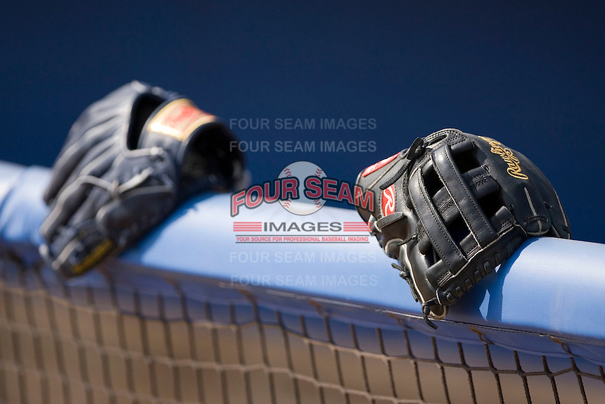 Two Rawlings fielders gloves sit on the top railing of the visitors dugout at Dodd Stadium in Norwich, CT, Tuesday, June 3, 2008.