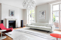 A tradiitional sitting room, which retains its original plasterwork cornice and Georgian windows, is furnished with a retro style white leather corner sofa and grey and white rug. A red chair and side table provide a spot of colour in the otherwise white room.