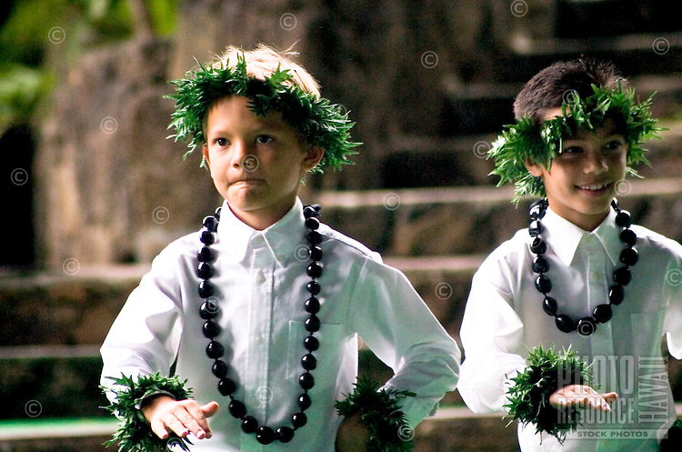 Two boys in white shirts and kukui nut leis dancing a modern hula