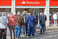 Pictured: A queue of people outside Santander Bank in the city centre of Swansea, south Wales, UK. Friday 20 March 2020<br /> Re: Covid-19 Coronavirus pandemic, UK.