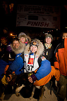 Rookie musher Rohn Buser poses at the finish line with his lead dogs & family including his dad, Martin, mother, Kathy, and brother, Nikolai, after finishing 37th during Iditarod 2008