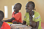 An older woman breastfeeds her infant as she sits in a classroom with other students in the Loreto Primary School in Rumbek, South Sudan. The Loreto Sisters began a secondary school for girls in 2008, with students from throughout the country, but soon after added a primary in response to local community demands. Some of the students are adults, and participate in an afternoon accelerated learning program.