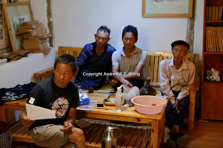 Wumu Village, Yulong County, Yunnan Province, China - Dongba priest He Jixian of the Naxi ethnic group explains to other villagers during the inaugural meeting of their agricultural cooperative, June 2019.