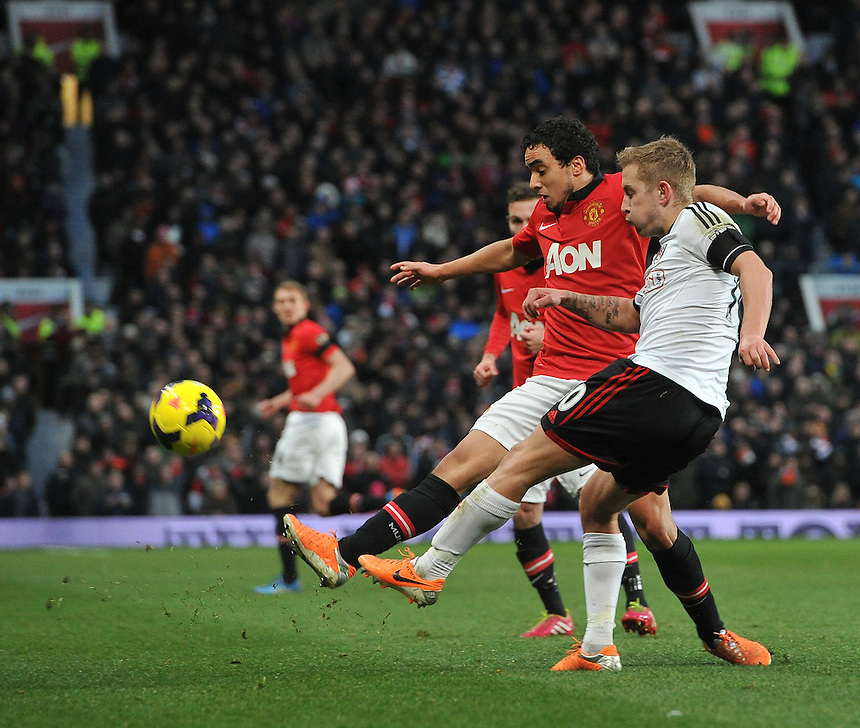 Fulham's Lewis Holtby clears under pressure from Manchester United's Rafael<br /> <br /> Photo by Dave Howarth/CameraSport<br /> <br /> Football - Barclays Premiership - Manchester United v Fulham - Sunday 9th February 2014 - Old Trafford - Manchester<br /> <br /> &copy; CameraSport - 43 Linden Ave. Countesthorpe. Leicester. England. LE8 5PG - Tel: +44 (0) 116 277 4147 - admin@camerasport.com - www.camerasport.com