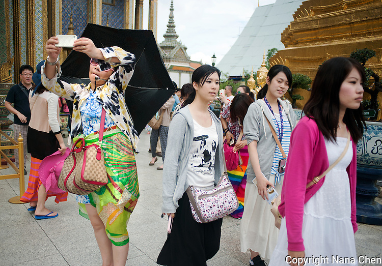 A Chinese tourist among her fellow travellers takes a photograph at the Grand Palace in Bangkok, one of the most popular attractions in the Thai capital.