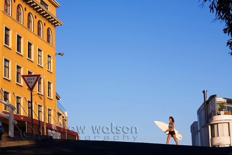 A woman carries her surfboard down to the beach at Bondi.  Bondi Beach, Sydney, New South Wales, AUSTRALIA.