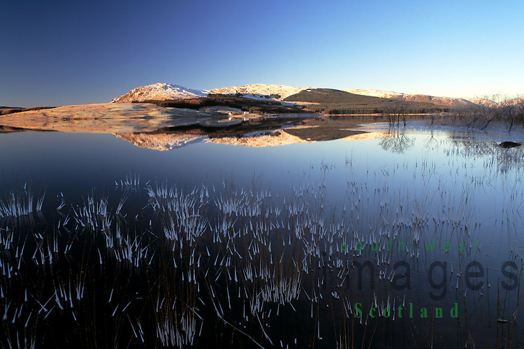 Winter landscape looking across a cold frozen Clatteringshaws Loch to Low Craignell and Darnaw in the Galloway Forest Park Dumfries and Galloway Scotland UK