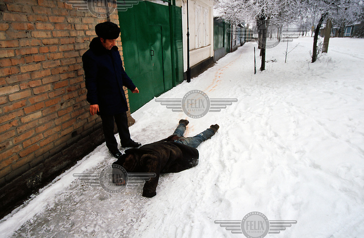 A man trying to drag another to safety after a mortar attack in central Grozny.
