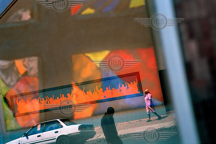People walk past a car by a street mural in Johannesburg.