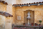 Monterey County, CA<br /> Alcove with Madona and Child framed with tiled roof lines in the courtyard gardens of the Carmel Mission Basilica (1797) - Mission San Carlos Borromeo del Rio Carmelo