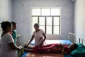 57 year old Usha Srivastava has been working as a mid wife for 36 years. Here she checks a pregnant woman, 25 year old Mehrul Nisha in the Public Health Centre in Adapur village of Raxaul district of Bihar.