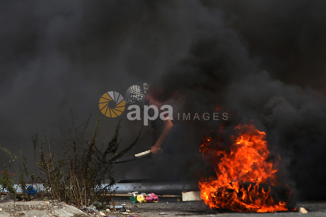 A Palestinian protester burns tires during clashes with Israeli security forces near the Jewish settlement of Bet El, near the West Bank city of Ramallah, on October 13, 2015. A wave of stabbings that hit Israel, Jerusalem and the West Bank this month along with violent protests in annexed east Jerusalem and the occupied West Bank, has led to warnings that a full-scale Palestinian uprising, or third intifada, could erupt. The unrest has also spread to the Gaza Strip, with clashes along the border in recent days leaving nine Palestinians dead from Israeli fire. Photo by Shadi Hatem